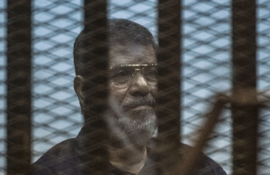 Egypt's deposed Islamist president Mohamed Morsi sits behind the defendant's cage as the judge reads out his verdict sentencing him and more than 100 other defendants to death at the police academy in Cairo on May 16, 2015. (KHALED DESOUKI/AFP/Getty Images)