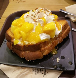 Mango Bread- 3 slices of toast are sandwiched together with chewy rice cake and topped with whipped cream, fresh mango chunks and syrup
